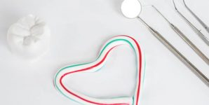 Dental instruments next to a heart outline made from toothpaste.