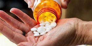 Close up of a hand handling prescriptions pills.