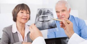 Male dentist explaining dental x-ray to senior couple in clinic.