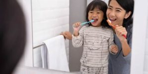 Mom and kid brushing their teeth together.