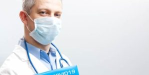 Dentist wearing face mask and holding folder that reads COVID-19.