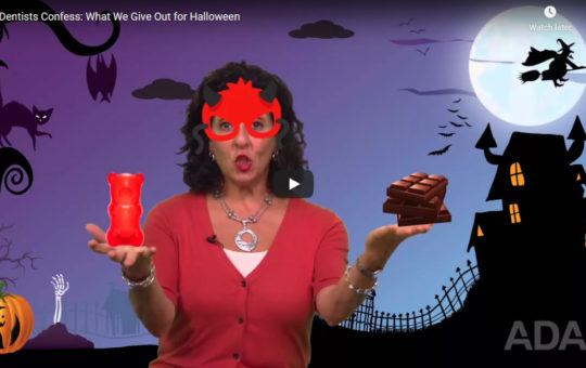 Opening screen from a video titled Dentists Confess What We Give Out for Halloween. Illustration of woman in a costume holding a gummy bear and chocolate bars.