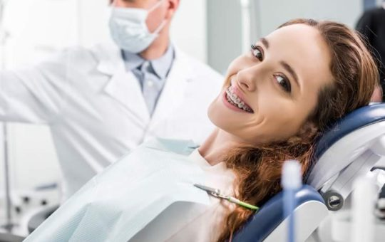 woman in braces during examination of teeth near dentist