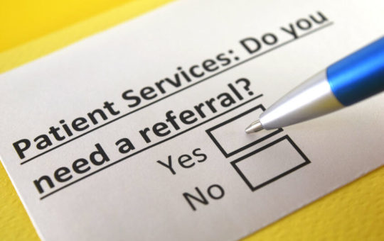 A photo illustration of a card that reads Patient Services. Do You Need a Referral? Yes? No?