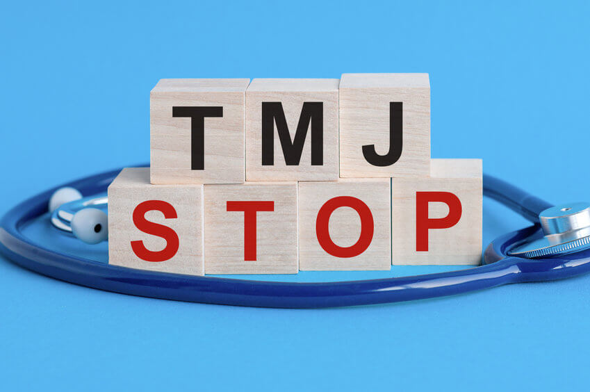Wooden block with words TMJ Stop - with stethoscope on the table